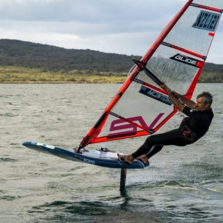 Flying effortless over the water on Starboard and Severne Windfoiling equipment in front of Rangitoto Island, Auckland, New Zealand